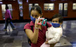 A Mexican woman and her child wear masks as she walks inside of a metro station in Mexico City April 25, 2009. (REUTERS/Jorge Dan Lopez)