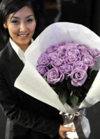 An employee of Japan's beverage giant Suntory holds a bunch of their genetically modified blue roses at a press conference in Tokyo. Japan's Suntory Ltd. said it would start selling the world's first genetically-modified blue roses next month, 20 years after it began research to create the novelty flowers